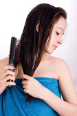 Woman is brushing her hair and looking down — Stock Photo