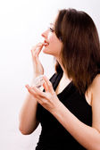 Cosmetic girl is touching her lips — Stock Photo