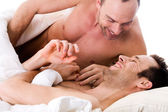 Smiling men couple in bed — Stock Photo