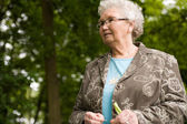 Grandmother standing outside looking — Stock Photo