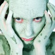 Hands on my green clay covered face — Stock Photo #12708728