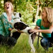 Sisters are playing with the dog — Stock Photo