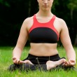 Practising yoga in a green field with trees — Stock Photo