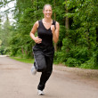 Sportive young woman running over a forrest road - Stock Photo