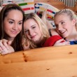3 adorable girlfriends cuddling in a bed — Stockfoto