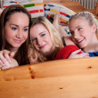 3 adorable girlfriends cuddling in a bed — Stock fotografie