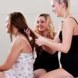 Foto Stock: Girs doing each others hair on bed