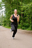 Sportive young woman running over a forrest road — Stock Photo