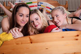 3 adorable girlfriends cuddling in a bed — Stock Photo
