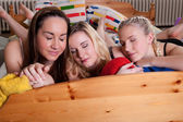 3 cute girlfriends being sleepy on a bed — Stock Photo