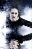 Frau mit lange lockigem haar kriechen aus rauch — Stockfoto