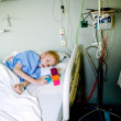 Sick boy in hospital bed looking dizzy at his toy — 图库照片