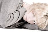 Sad looking beautiful girl lying on the floor looking at you — Stock Photo