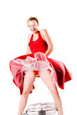 Funny girl in red gala dress playing with a ventilator laughing — Stock Photo