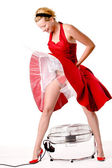 Funny girl in red gala dress standing over a ventilator — Stock Photo