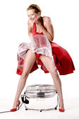 Funny girl in red gala dress being playful with a ventilator — Stock Photo