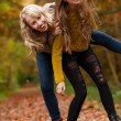 Smiling sisters in the forest - Stock Photo
