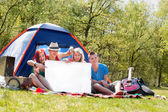 Youth on a camping with an empty sign board — Stock Photo