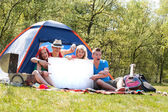 Teenagers on a camping with an empty sign board — Stock Photo