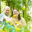 Happy young married couple between flowers — Stock Photo