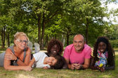 Ethnic family on the grass — Stock Photo