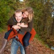 Young couple is riding piggyback — Foto de Stock