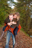 Young couple is riding piggyback — Stock Photo