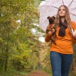 Fashion girl with a dog in the forest — Stock Photo