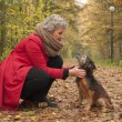 Stock Photo: Ager womand her cute dog in forest