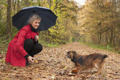 Woman with umbrella playing with her dog — Stock Photo