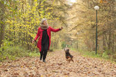 Middle aged lady is playing with her dog — Stock Photo