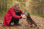 Retired woman in the forest with her pet — Stock Photo