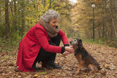Retired woman is caring of her dog — Stock Photo