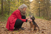 Ager woman and her cute dog in the forest — Stock Photo