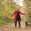 Stock Photo: Smiling middle aged womin forest with her dog
