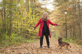 Smiling middle aged woman in the forest with her dog — Stock Photo