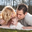 Young parents are kissing the baby — Stok fotoğraf