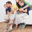 Young family playing videogames — Stock Photo #12439936