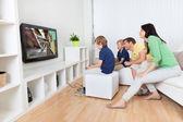 Ung familj spelar videospel — Stockfoto