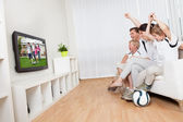 Young family watching football — Stock Photo