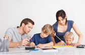 Parents helping their children with homework — Zdjęcie stockowe
