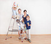 Young couple painting wall at home — Stock Photo