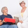 Laughing senior couple with red gift box — Stock Photo #12720118
