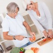Middle-aged couple preparing a meal - Stock Photo