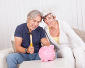 Senior couple raiding a piggybank — Stock Photo