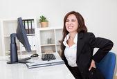 Geschäftsfrau, die mit rückenschmerzen bei der arbeit — Stockfoto