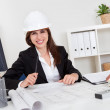 Businesswoman In Hardhat With Blueprints — Stock Photo #12765482
