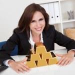 Businesswoman Holding Gold Bar — Stock Photo #12765495
