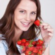Woman enjoying a bowl of strawberries — Stock Photo