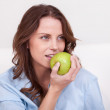Woman eating a healthy green apple — Stock Photo #12778050